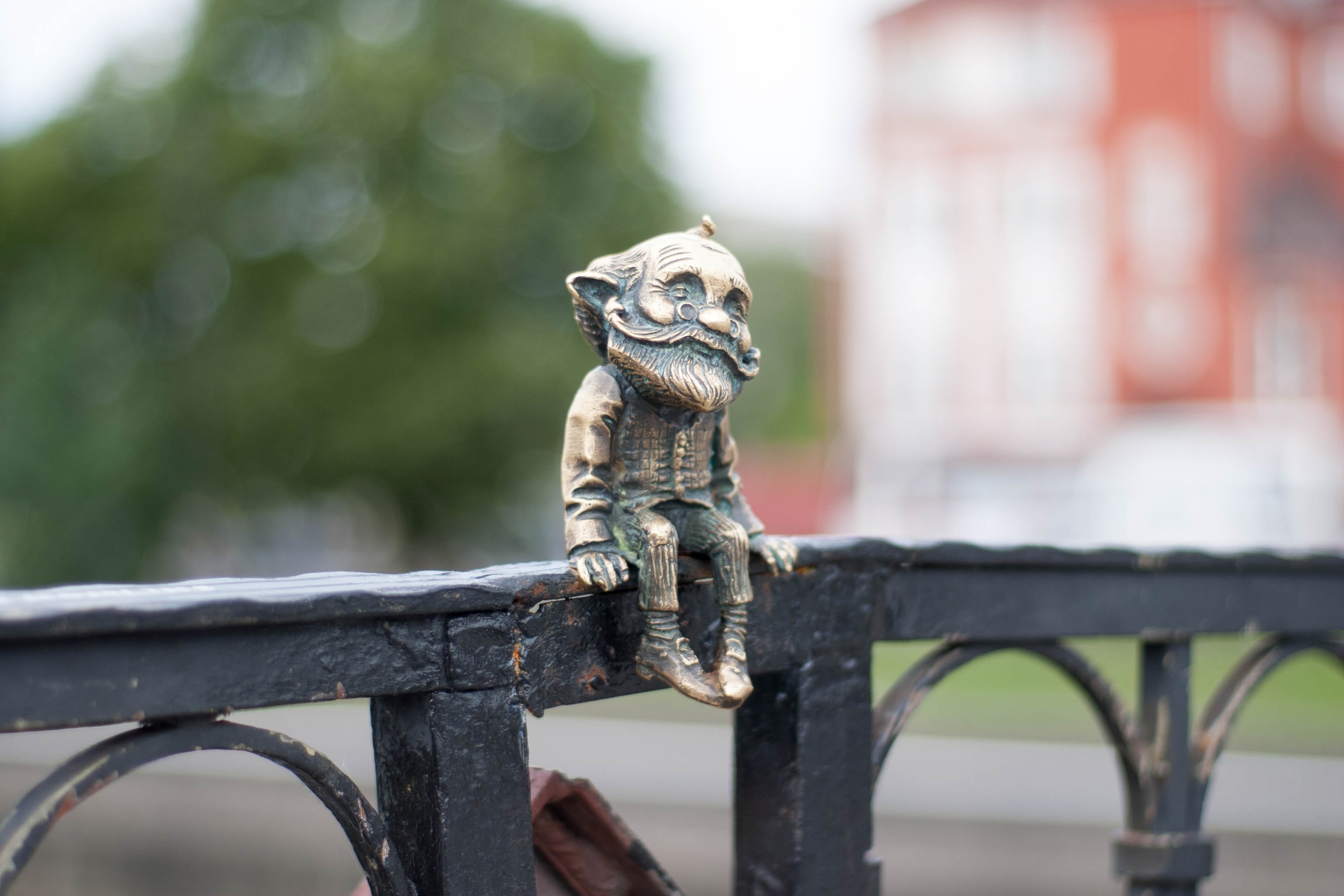 man figurine on grey wooden handrail