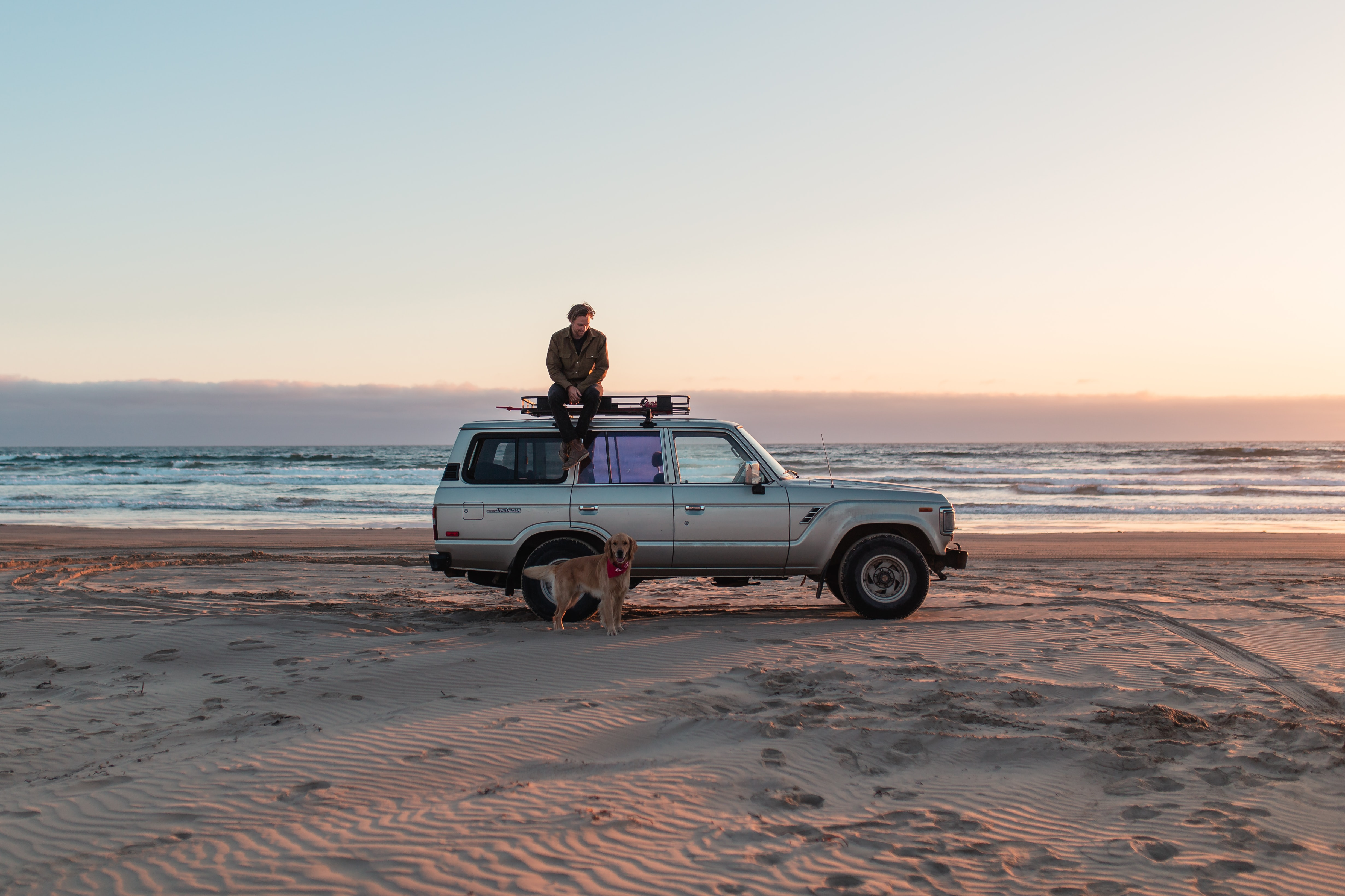 man sitting on gray SUV roof near seashore at sunset