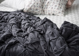 closeup photo of gray comforter on bed