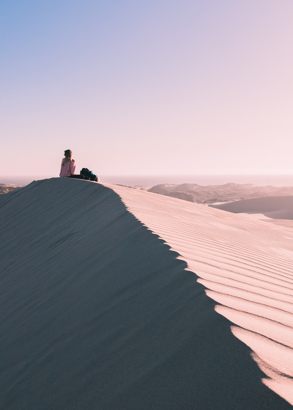 rule of thirds photography of person sitting on desert