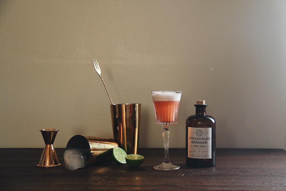 brass-colored cocktail shaker near bottle