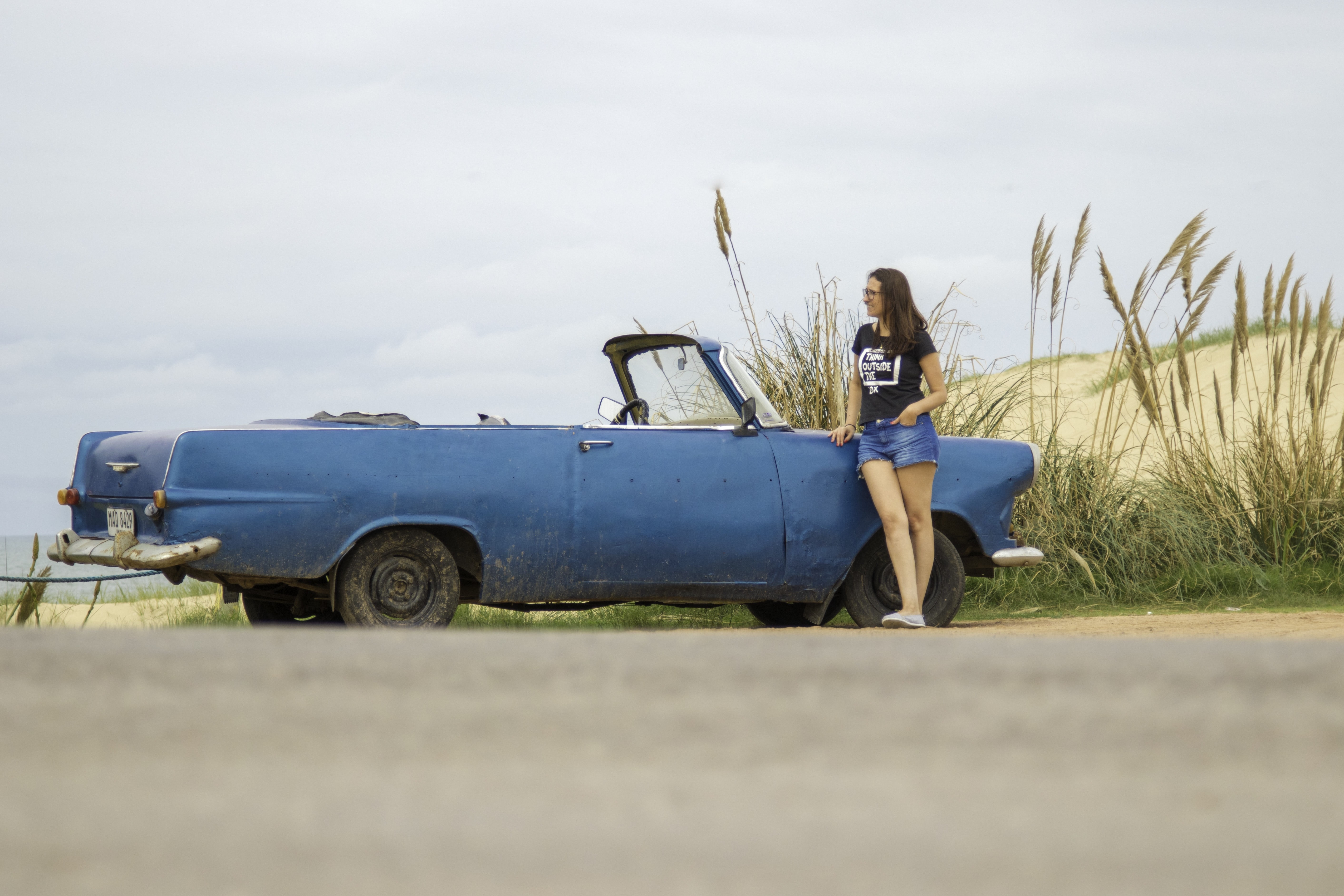 woman leaning on blue convertible coupe