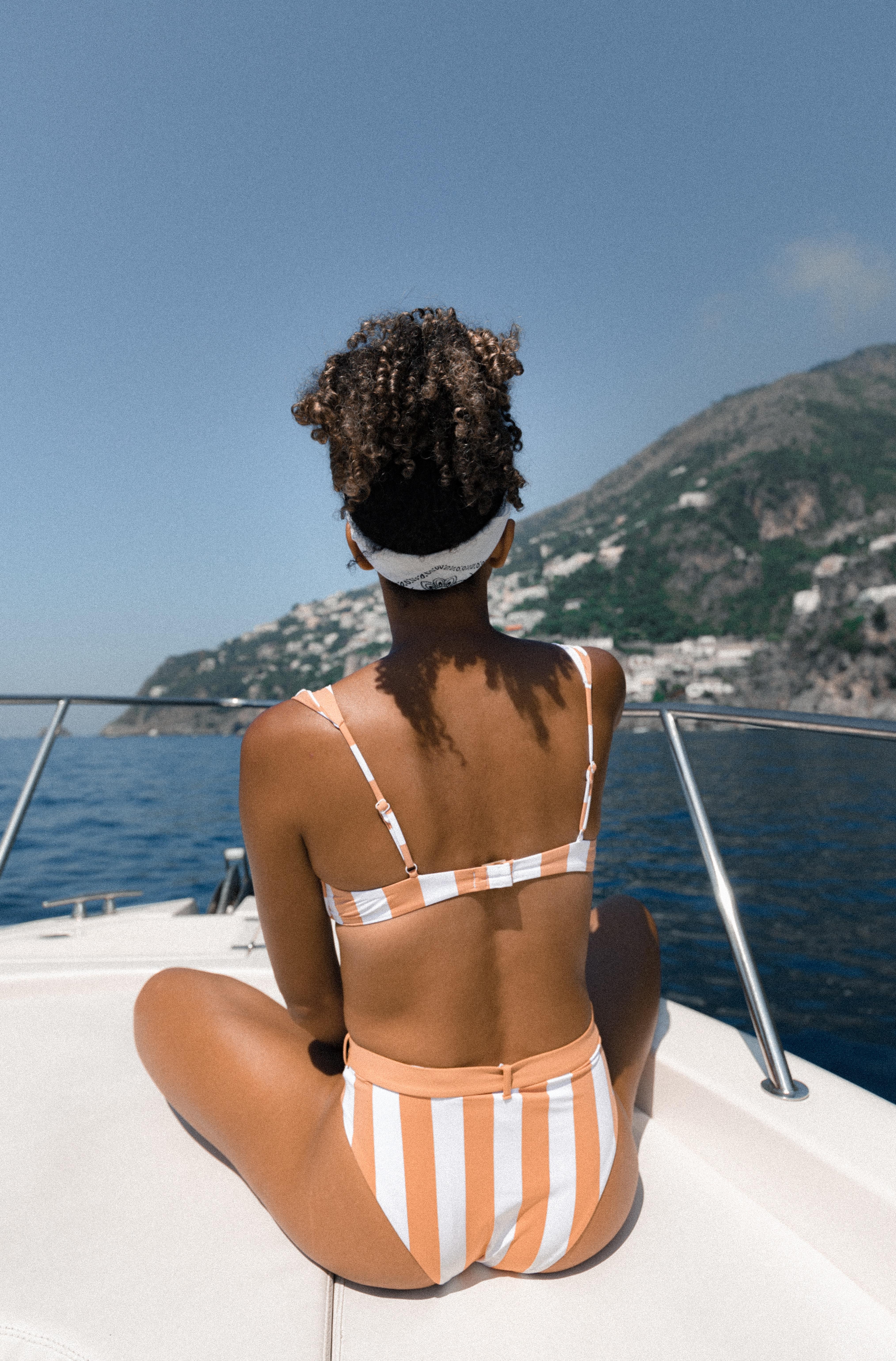 woman wearing white-and-brown bikini set while sitting on boat watching island