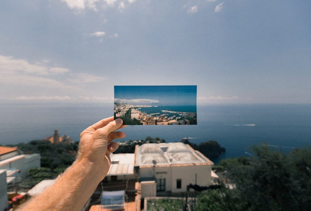 person holding photo of a city