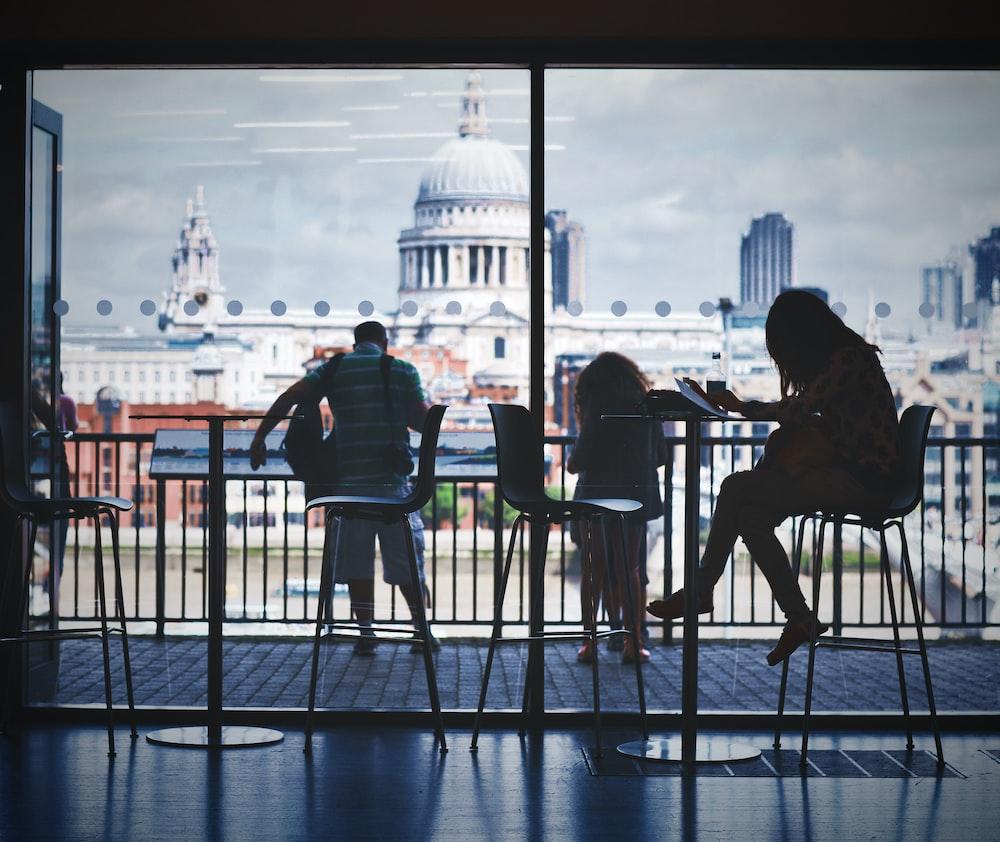 three person sitting while watching Washington DC Capitol