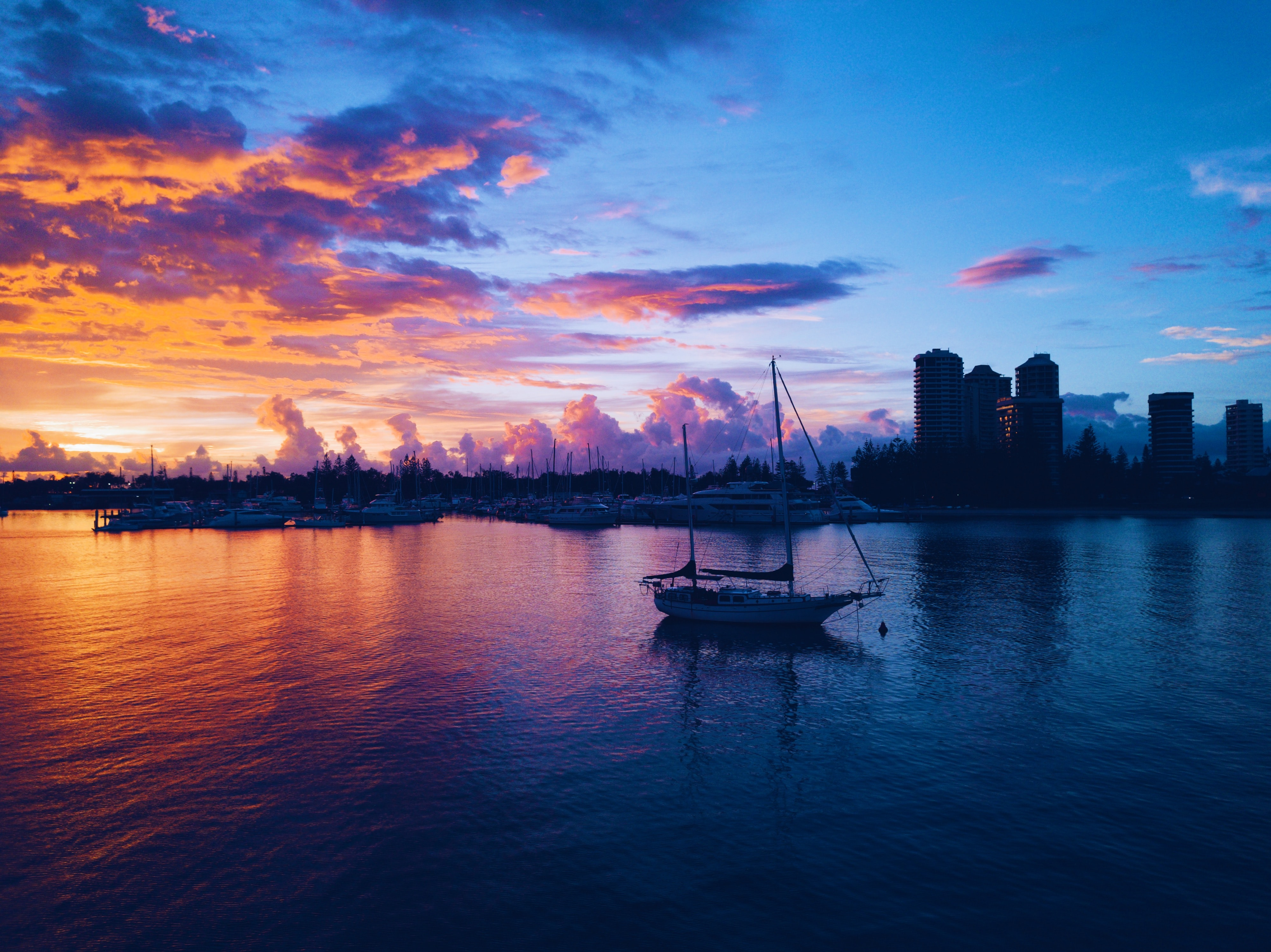 silhouette of boat on body of water near high rise buildings during golden hour