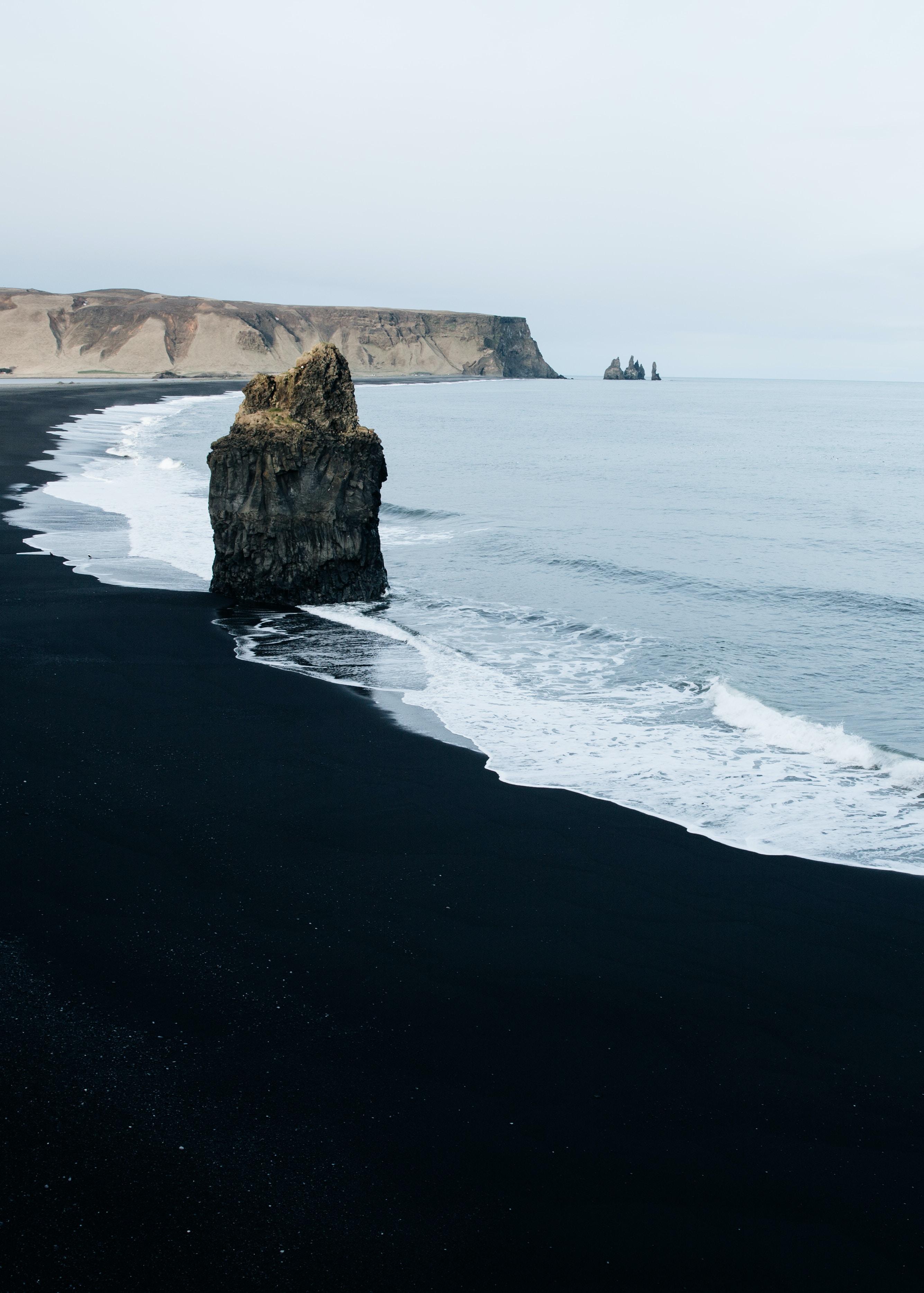 brown monolith rock on seashore