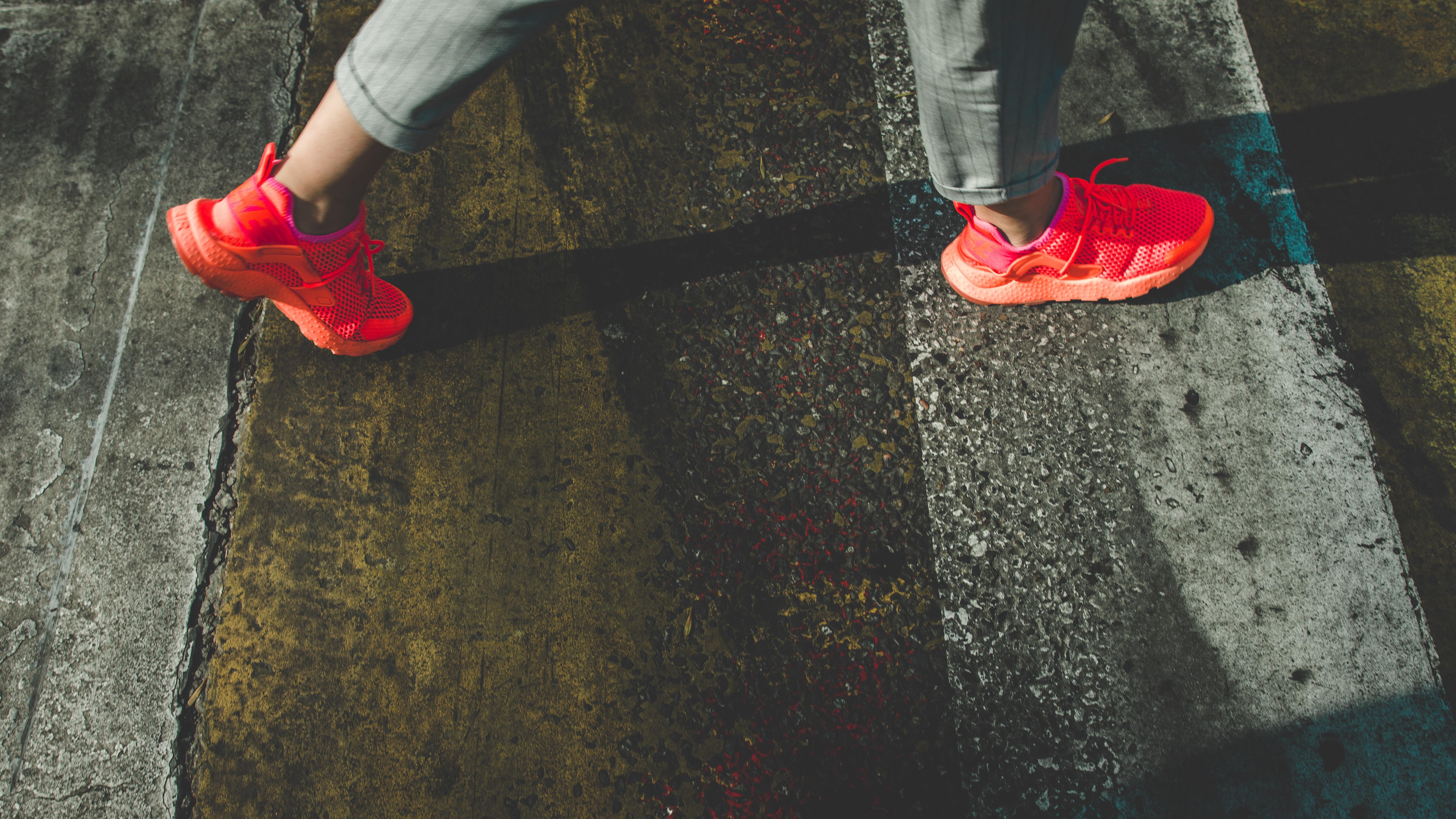 closeup photo of person wearing red Nike Air Huarache shoes