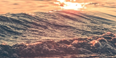focus photography of sea wave during sunset