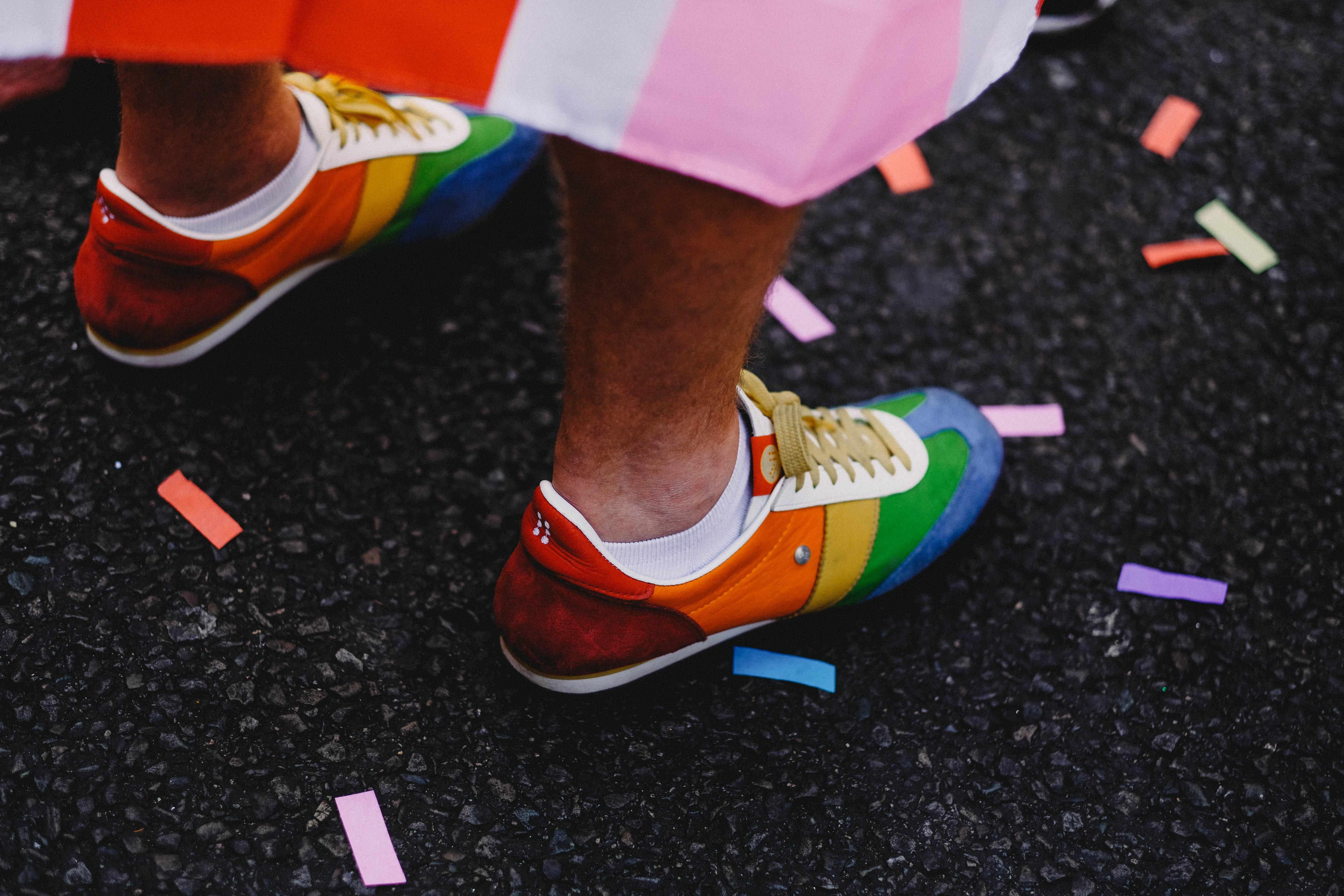 person wearing multicolored low-top shoes standing on ground
