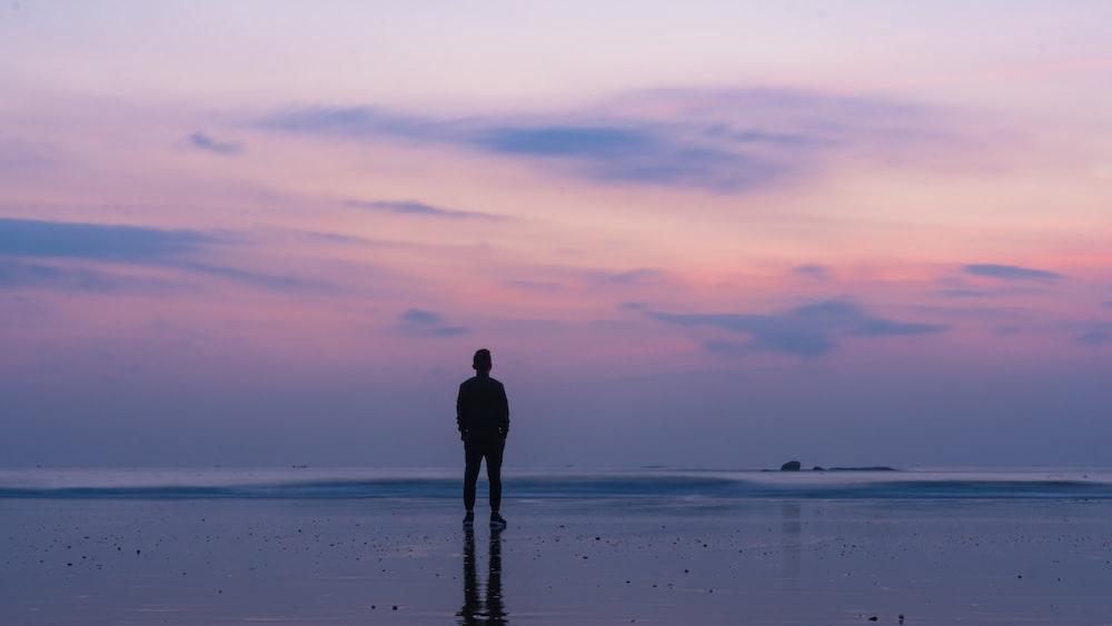 silhouette of man standing on seashore