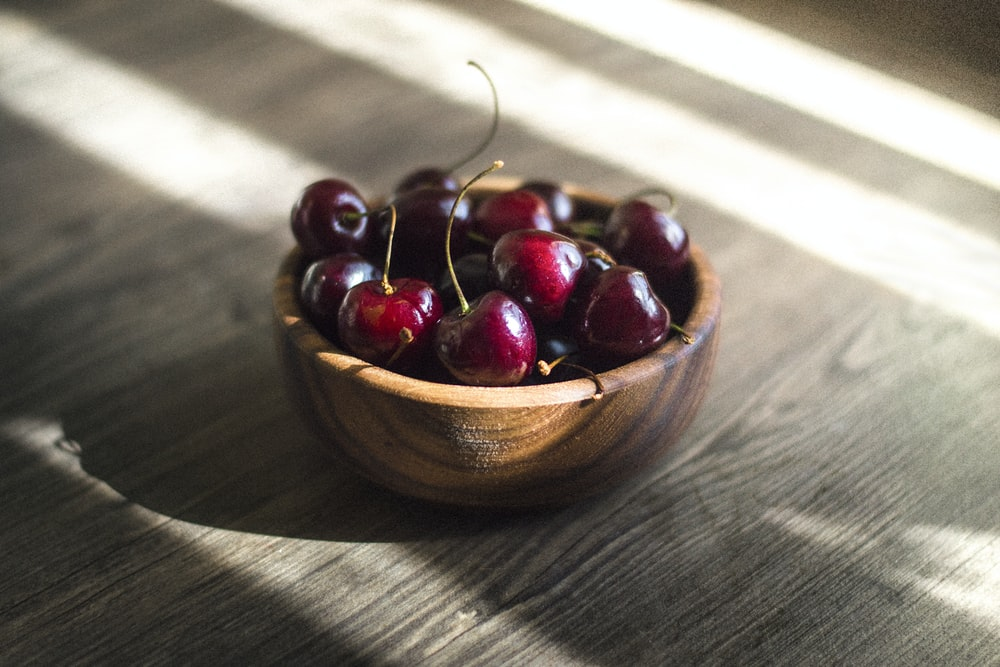bunch of red cherries in brown bowl