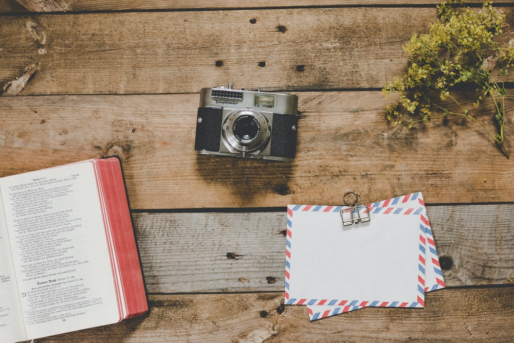 gray and black camera beside open book, green leafed plant, and white airmail envelopes