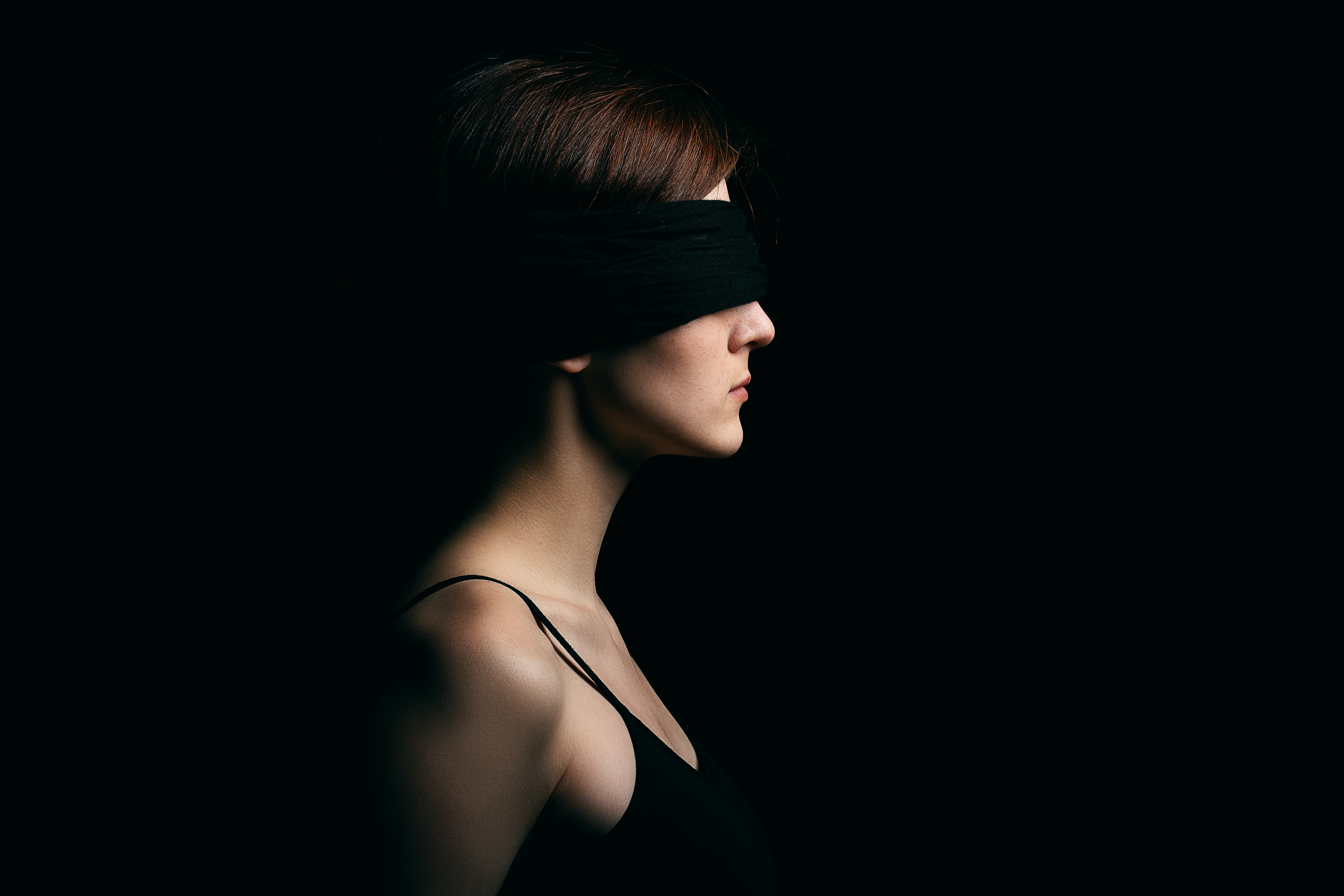 woman wearing black blindfold facing sideways