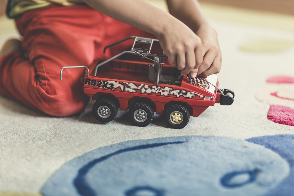 person playing red and black vehicle toy