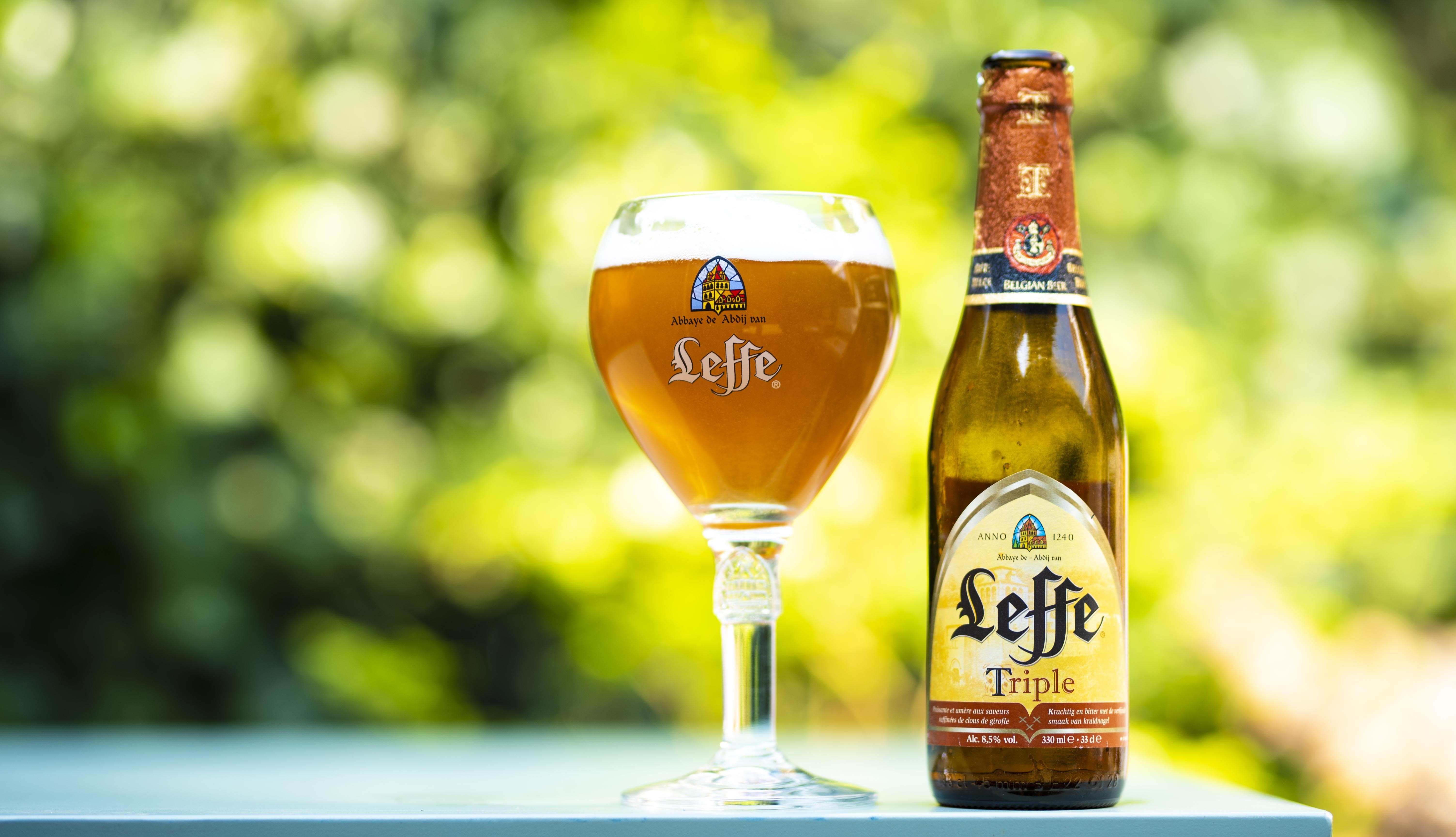 selective focus photo of Leffe triple glass bottle beside filled wine glass at daytime
