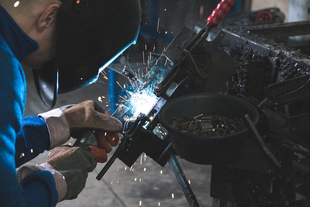 man welding a black metal