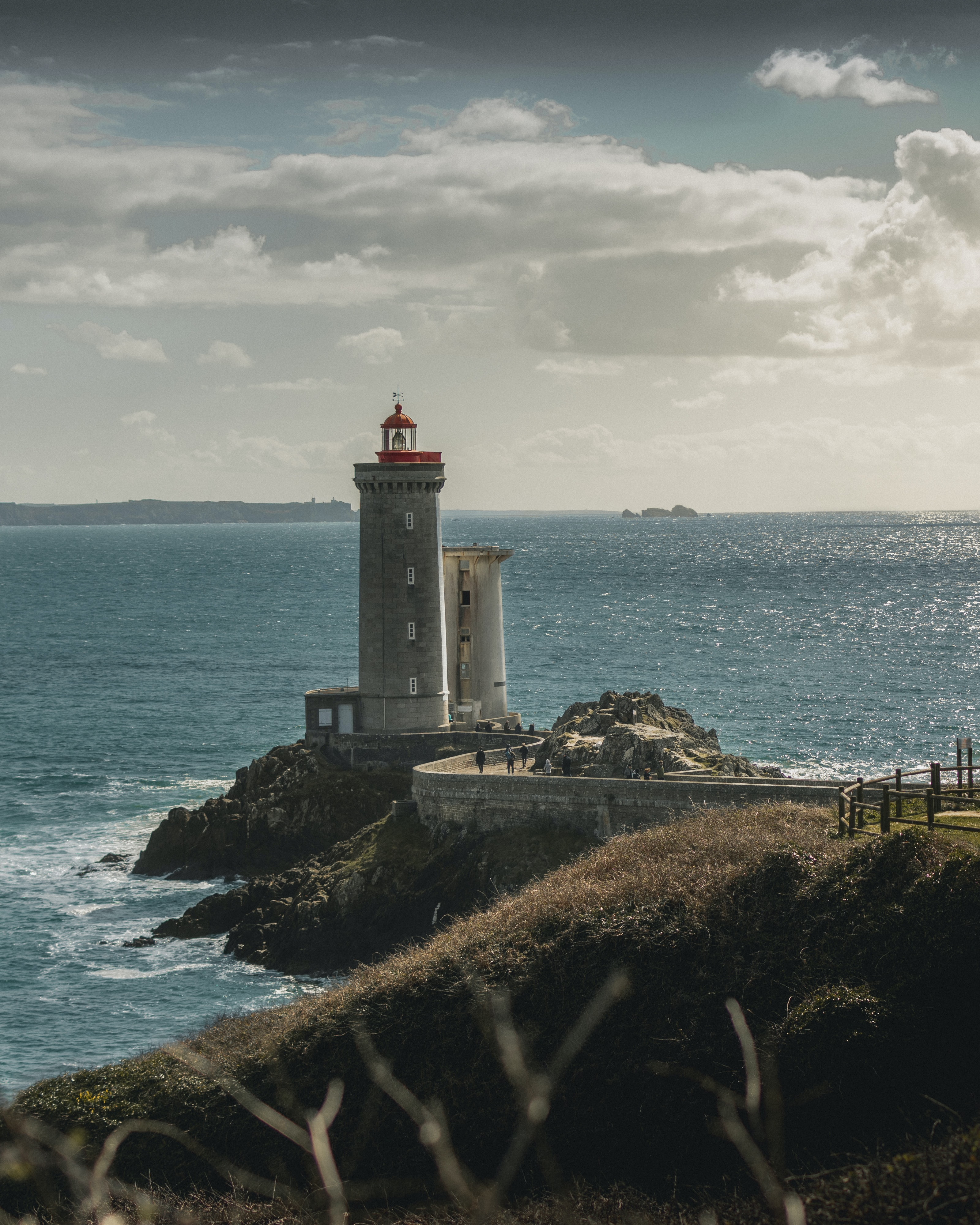 white and grey light house under blue sky during daytime