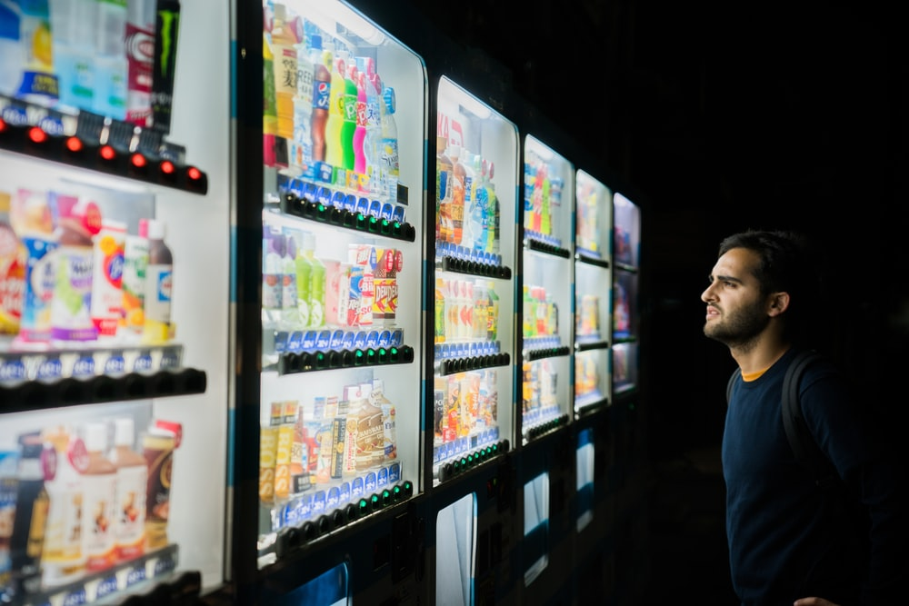 man on front of vending machines at nighttime