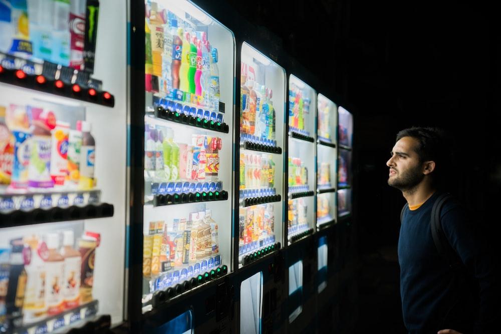 man choosing a soda from vending machine
