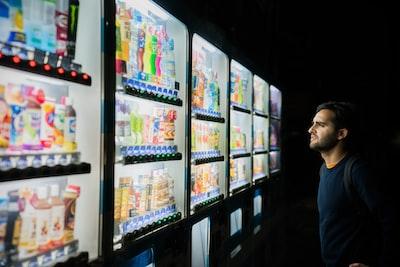 自動販売機でどの飲み物を購入するか迷っている男性