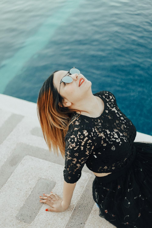 smiling woman looking upwards near sea
