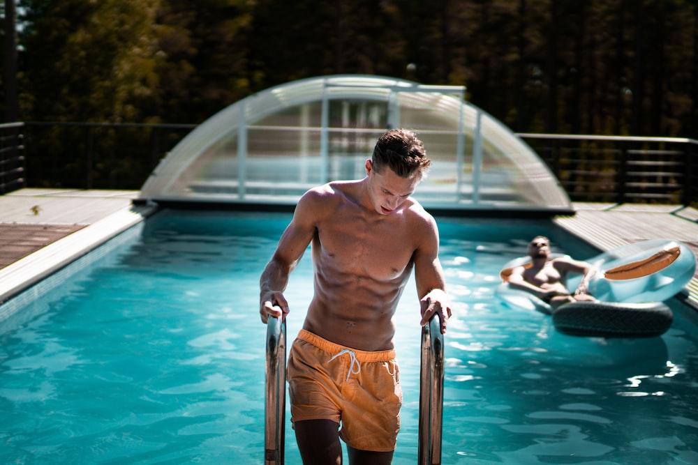 man holding grey steel swimming pool ladder