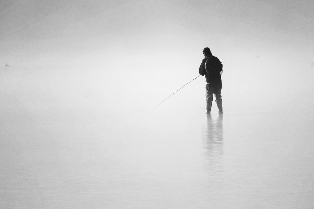 On a misty morning the fisherman wades out to catch some fish. Peace and tranquility.  The fisherman and water extremely still and calm.