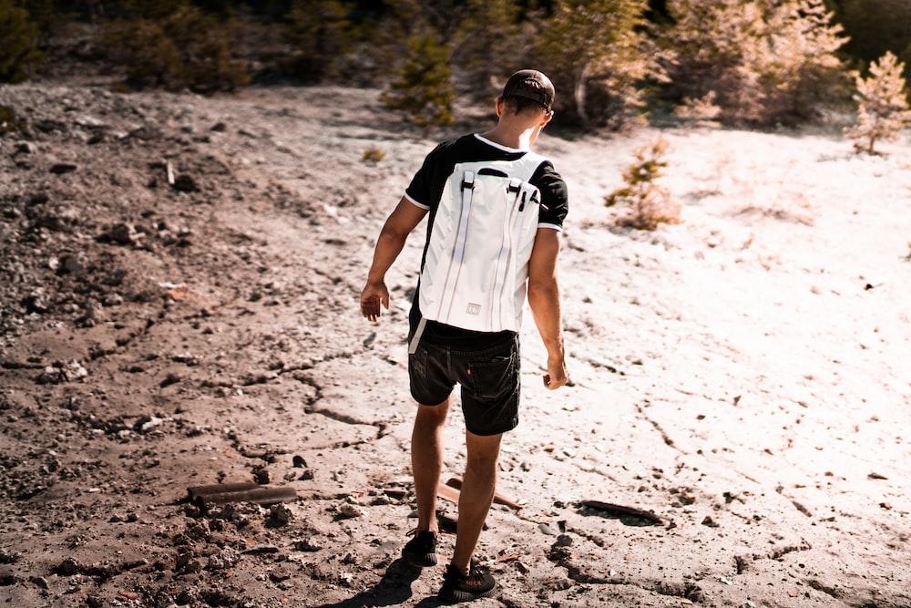 man walk on dry soil during daytime