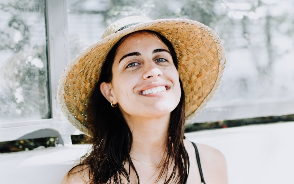 woman wearing black strap top with sunhat