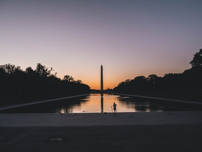 silhouette photo of person standing near body of water lincoln memorial teams background
