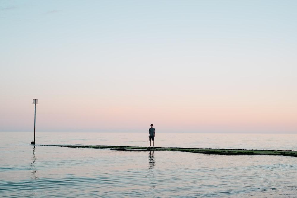 man standing on dock between body of water