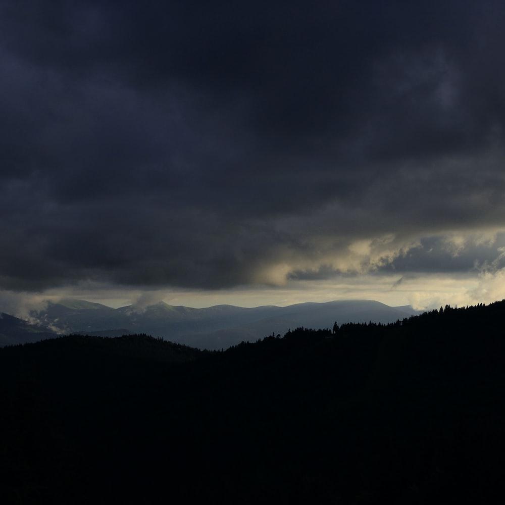 silhouette of mountain under gloomy sky