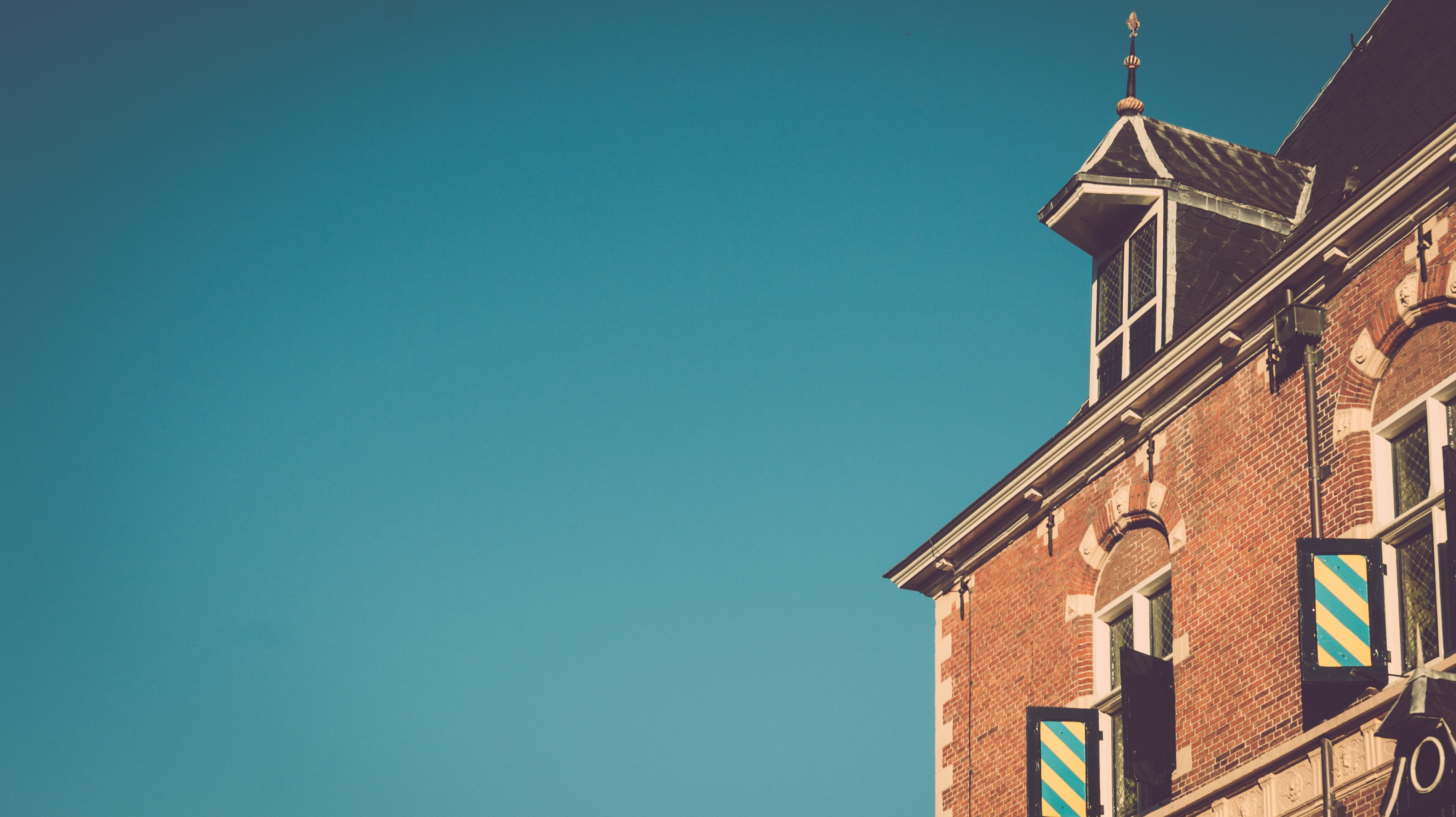 brown brick building under blue skies