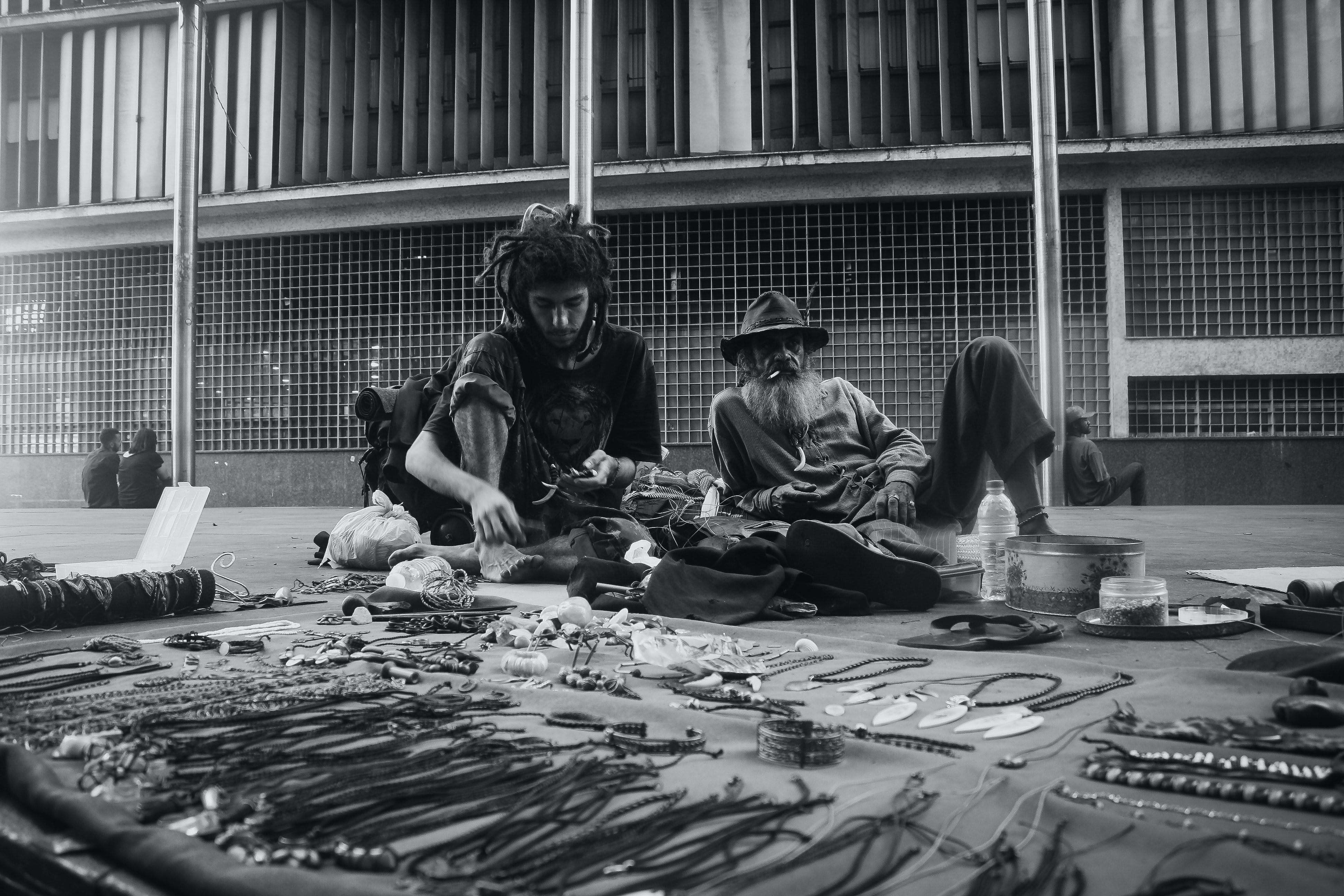 grayscale photo of two man sitting on the ground