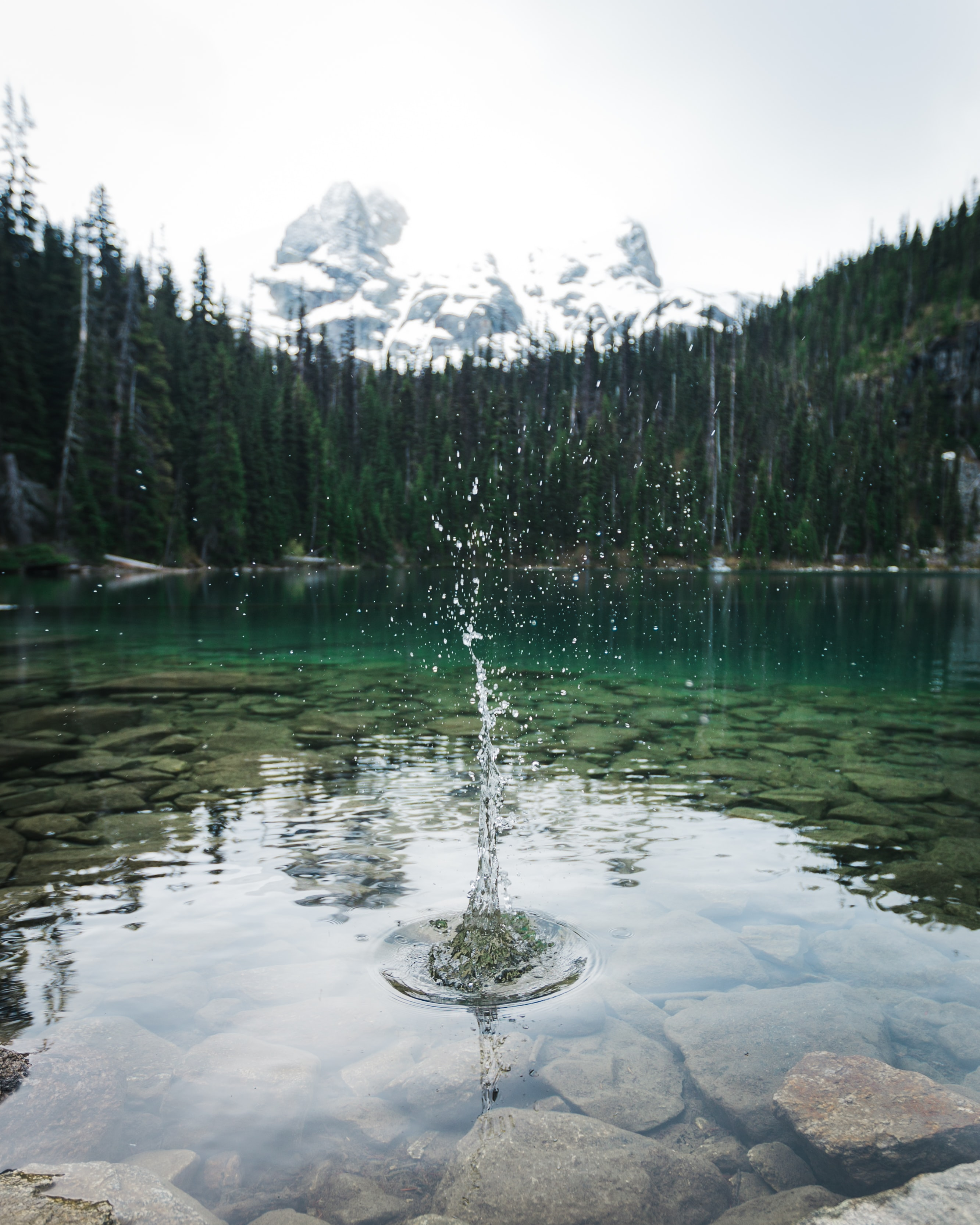 time lapse photography of uplift water on lake surrounded with at daytime