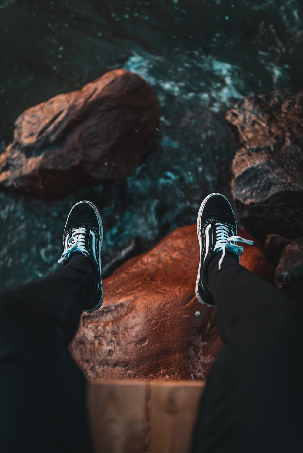high-angle of person sitting on cliff