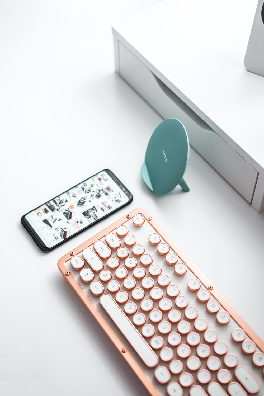 black smartphone beside computer keyboard