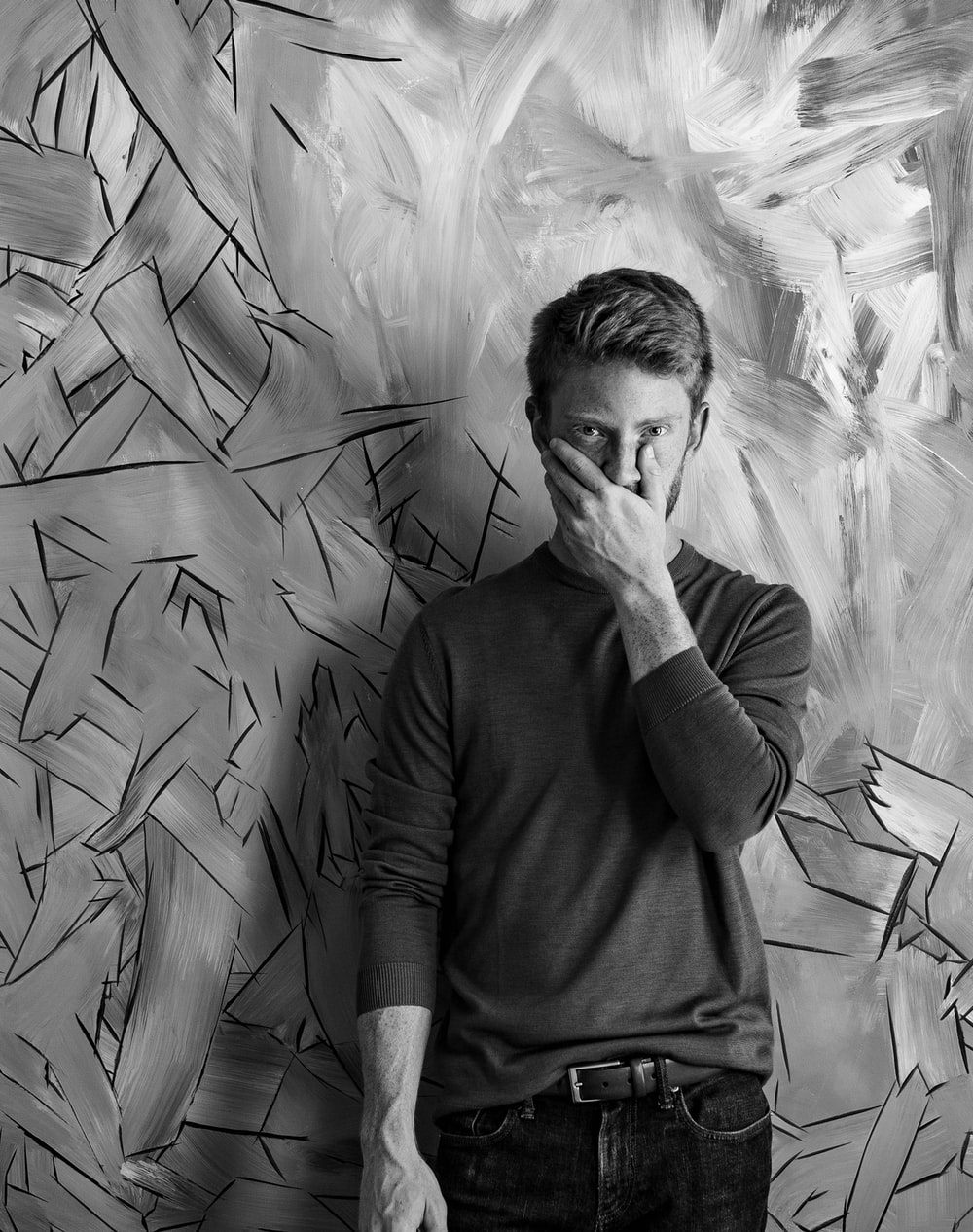 man standing against the wall holding his face
