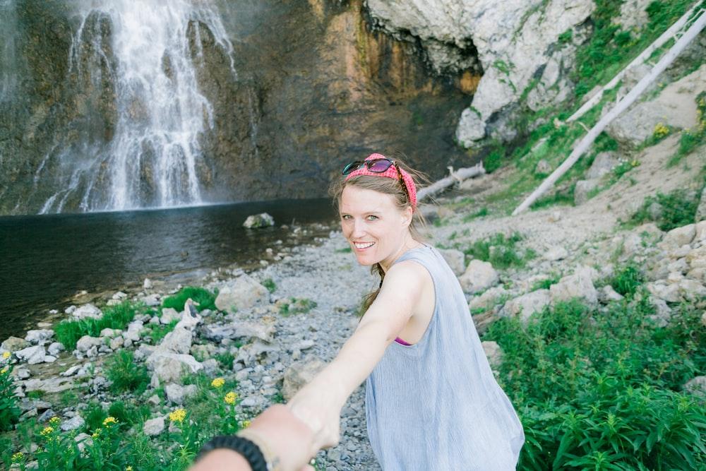 woman standing far away from waterfall