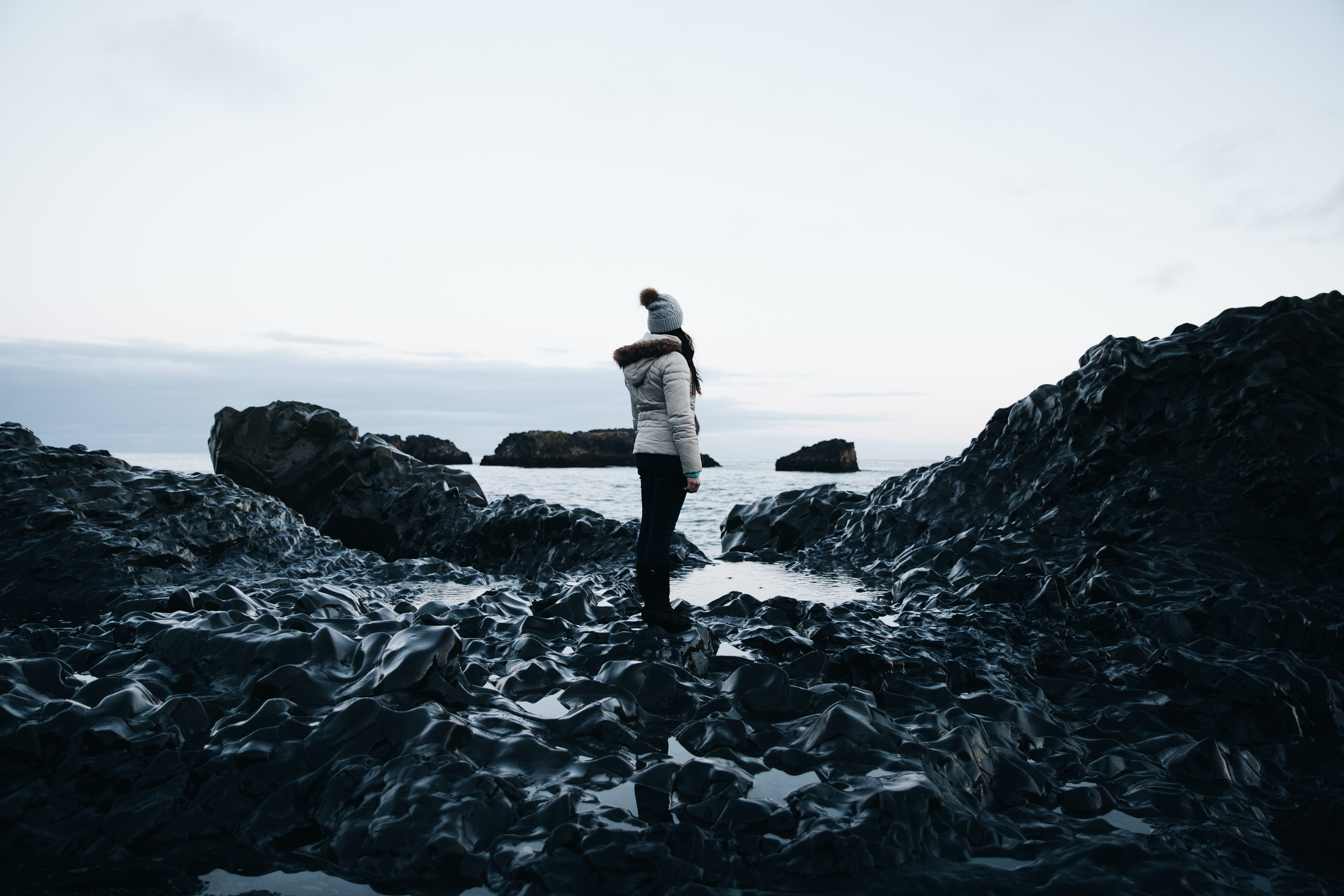 woman in hooded jacket standing on boulder looking at body of water