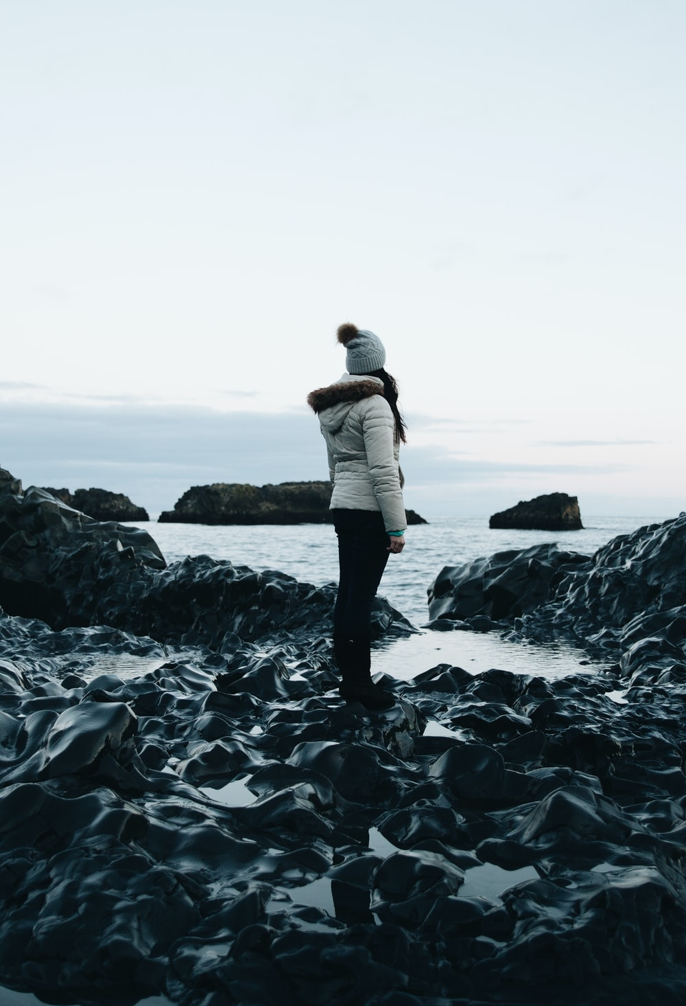 woman in white parka jacket and black pants outfit standing on rocks near body of water under white sky at daytime