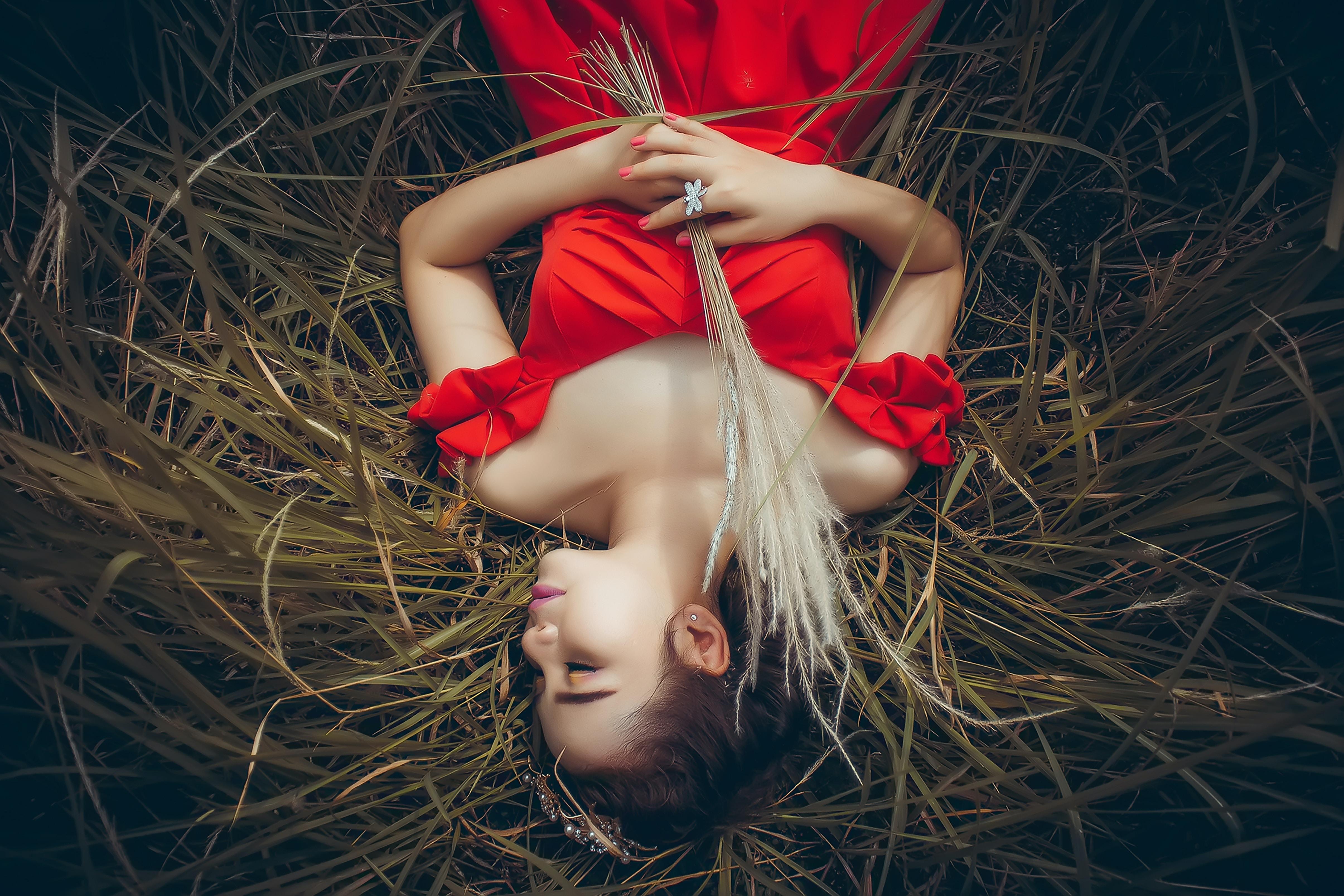 woman lying on green grass field