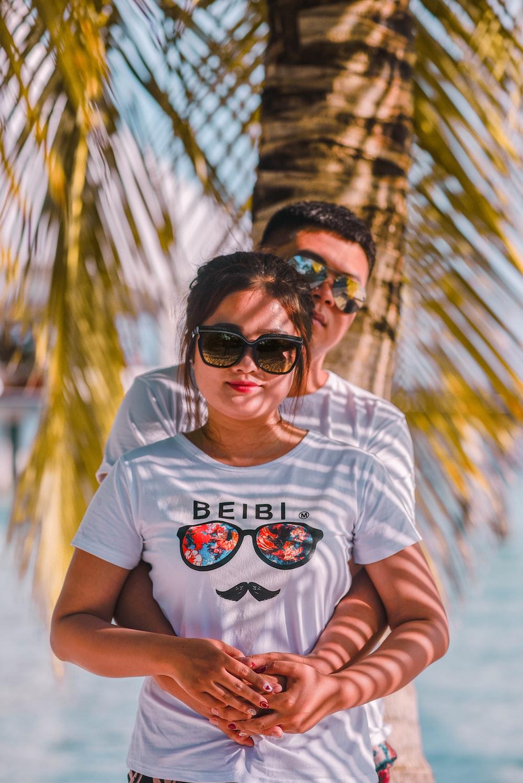 man hugging woman near coconut palm tree