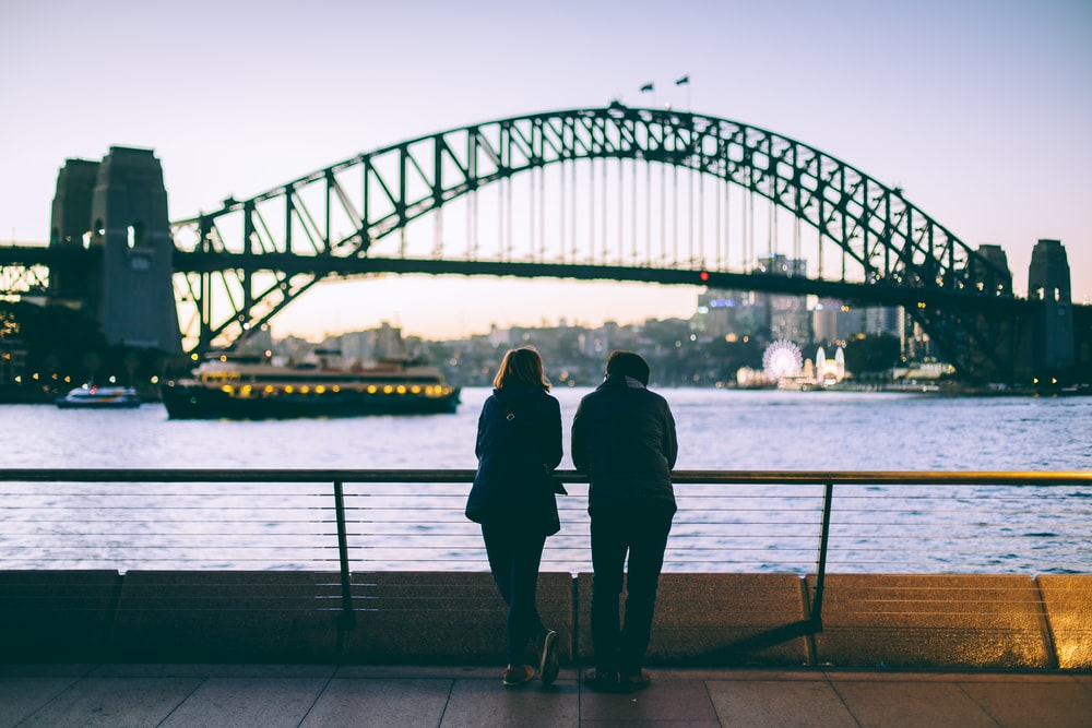 man and woman standing beside each other in front of body of water
