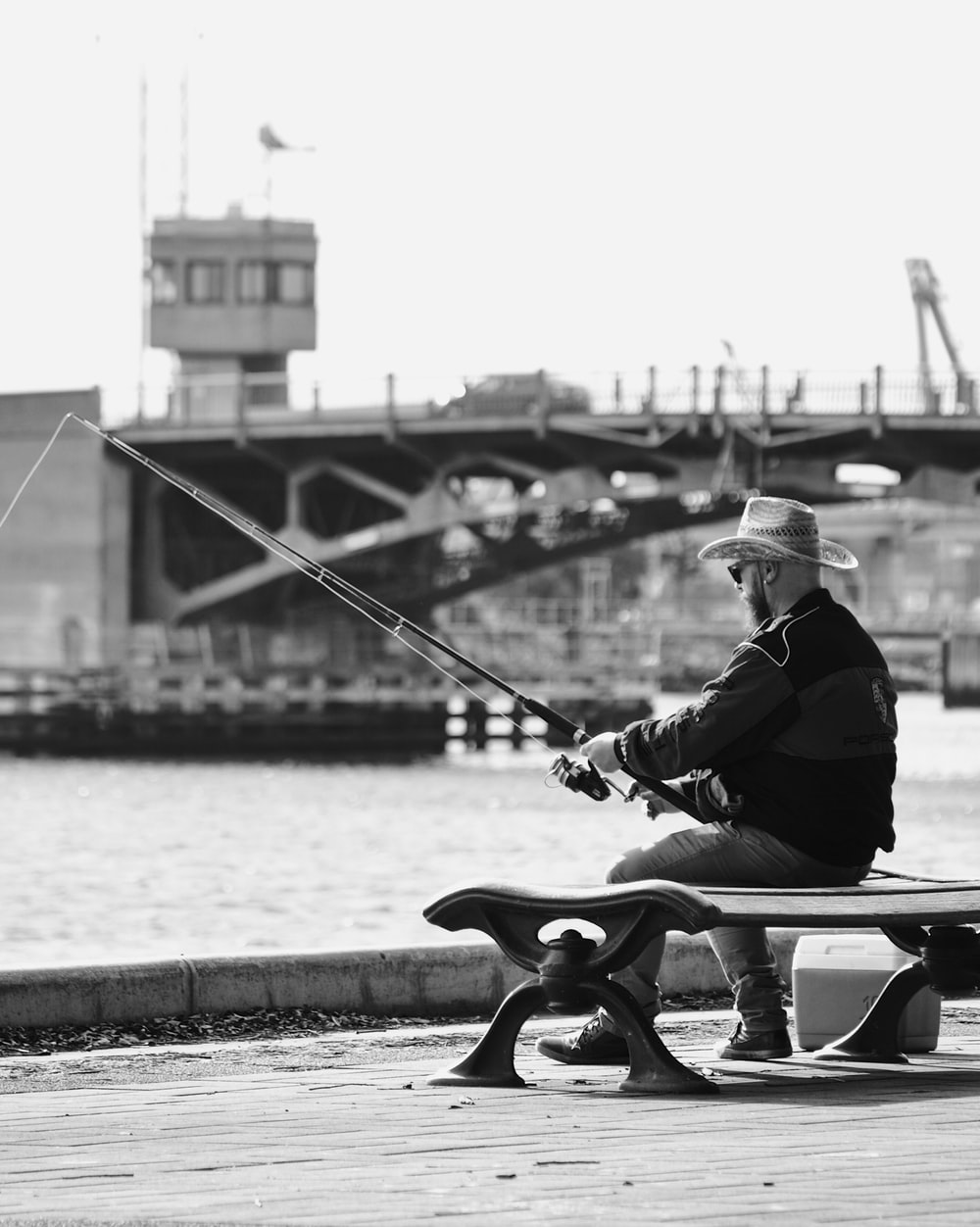 grayscale photo of a man while fishing