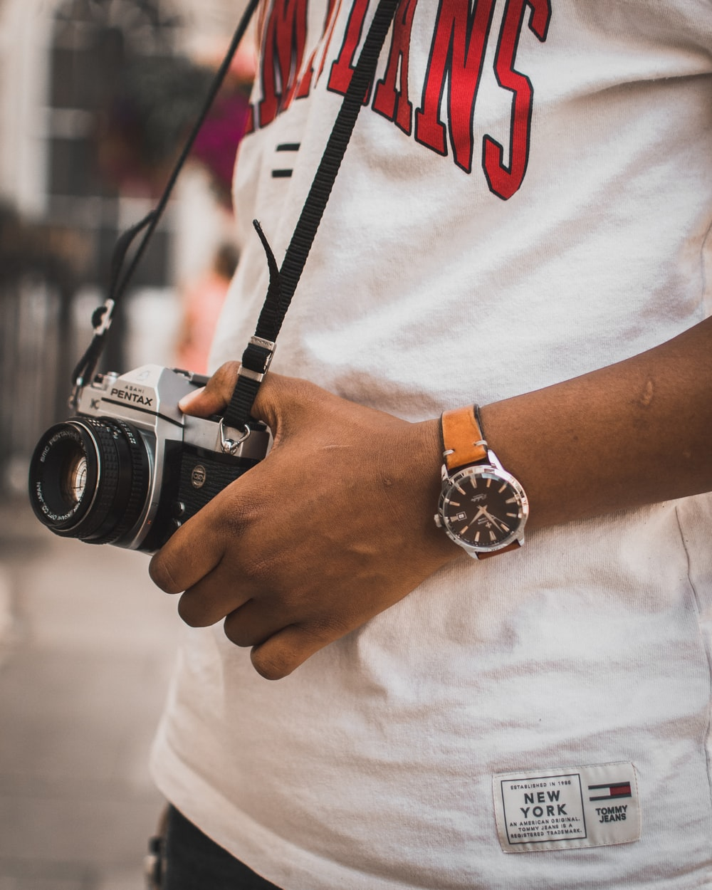 person carrying black and silver Pentax camera