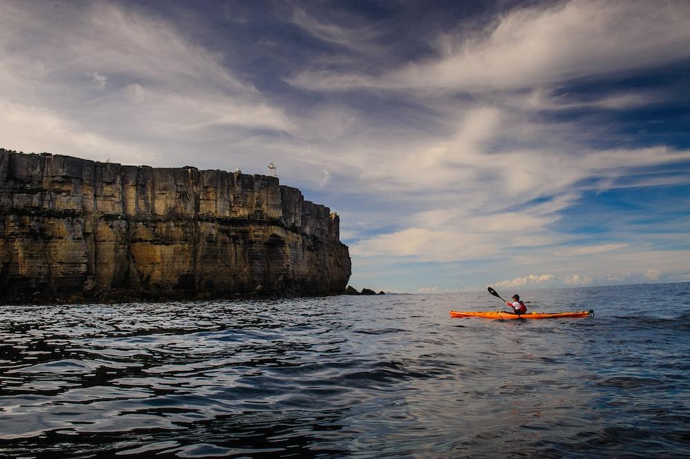 person riding kayak on sea near island
