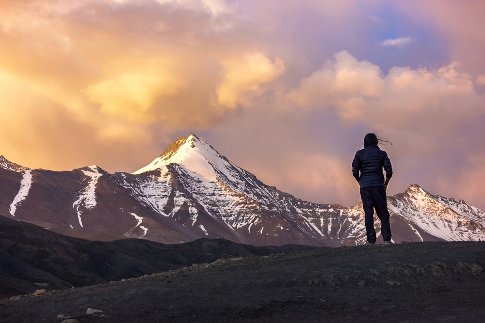person at the top of mountain facing another mountain