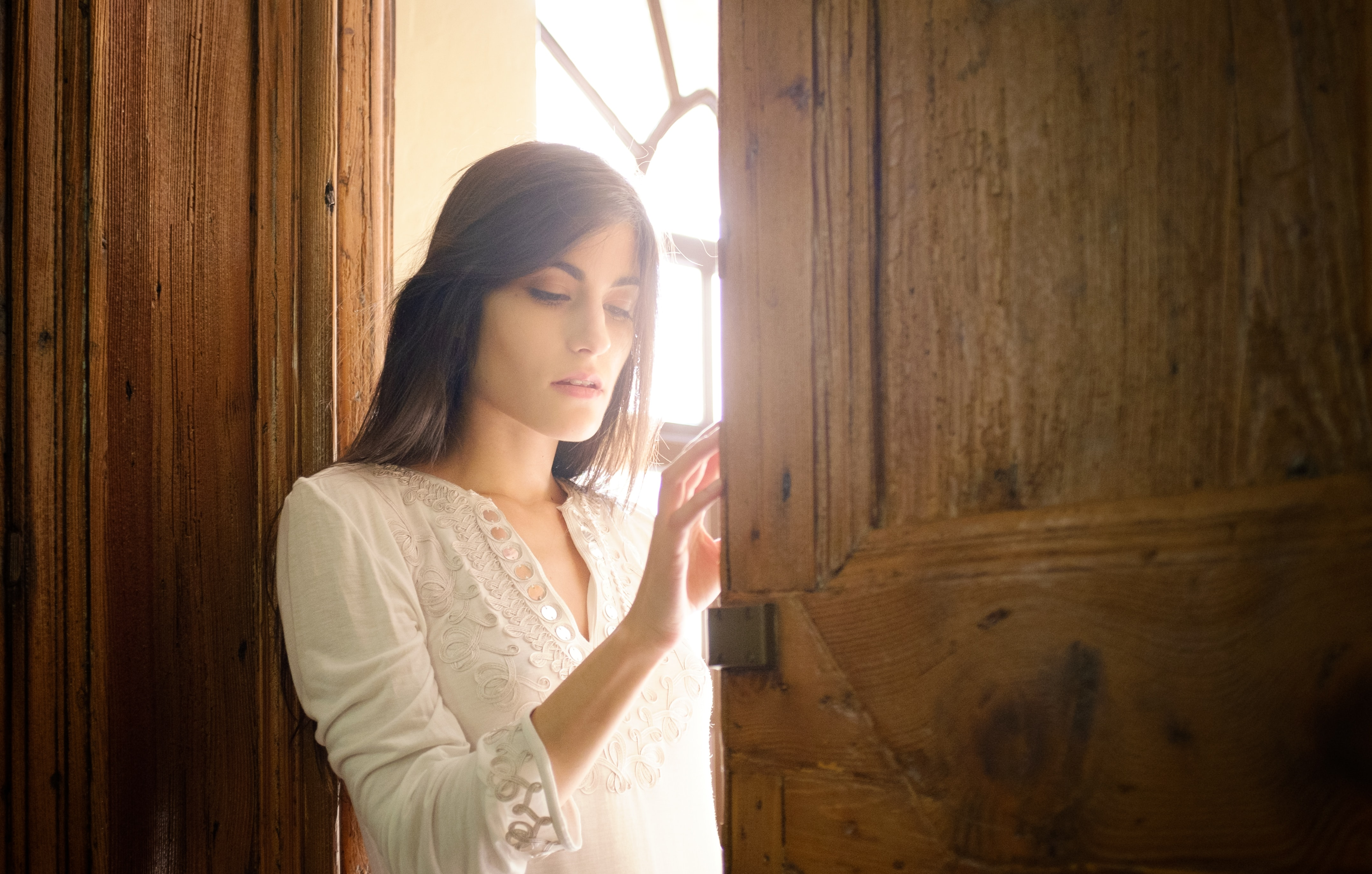 woman leaning on brown wooden door frame